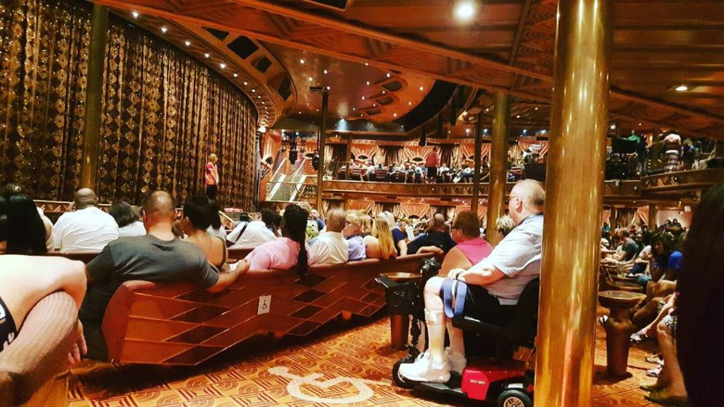 passengers sitting in cruise lounge hearing safety briefing
