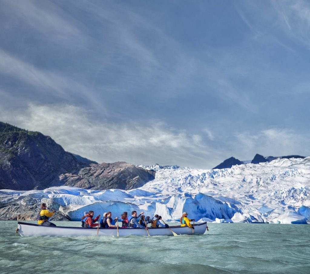 Visitors rowing a canoe to visit Mendenhall Glacier on a Norwegian Cruise